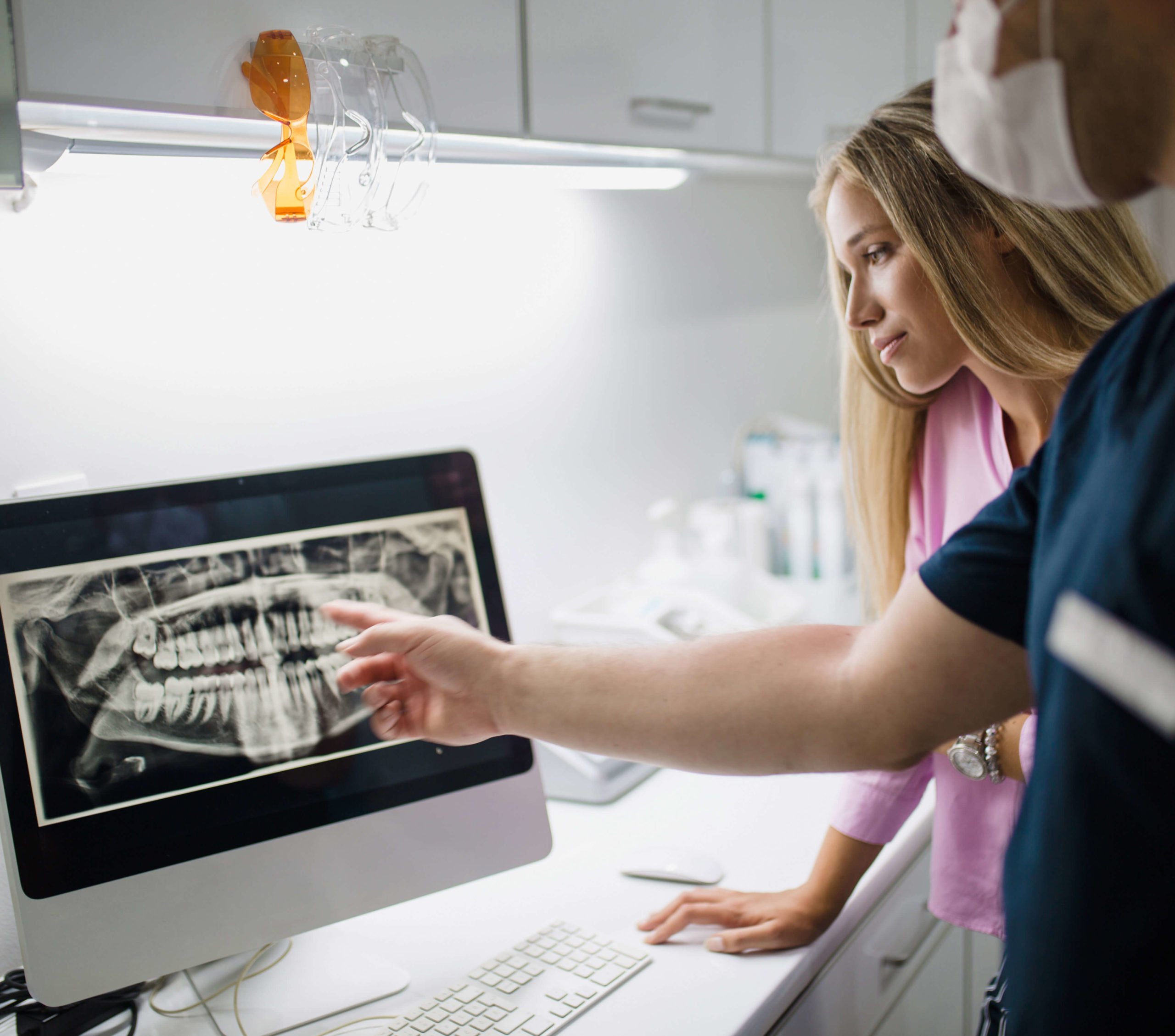 Two healthcare professionals reviewing an x-ray on a monitor